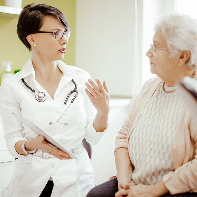 Practitioner speaking with older patient